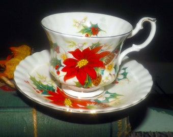 Vintage (1976) Royal Albert Poinsettia Christmas tea set (footed cup with saucer).  Red, white poinsettias, pine cones, holly, berries.