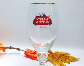 Vintage (1980s) Stella Artois footed goblet | stemmed beer pint glass. Etched-glass branding, professional dispensing mark. Gold rim.