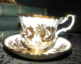 Vintage (1960s) Royal Albert Golden Rose tea set (footed cup with matching saucer).  Gold roses, brushed-gold edge and accents.