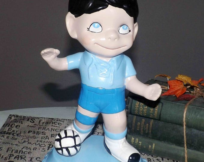 Vintage (1980s) ceramic figurine of a young, male soccer player in uniform, soccer ball at feet. Cute kids' decor.