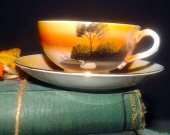 Early mid-century (1940s) Nippon hand-painted tea set (flat cup with matching saucer). Landscape of trees, orange sky, swan.