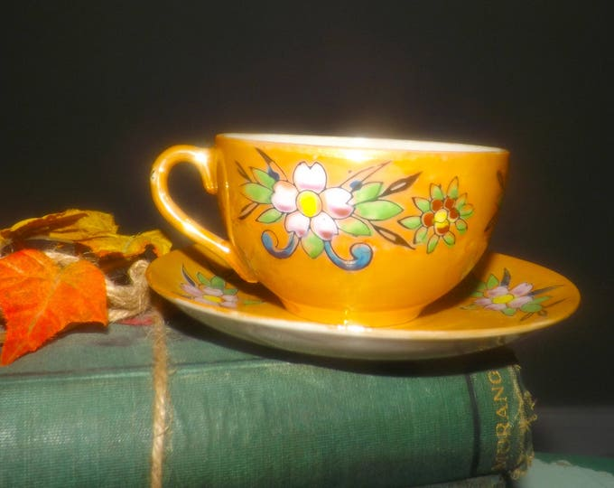 Mid-century (1950s) lusterware tea set (flat cup with matching saucer). Japan | Nippon. Bright multicolor florals on mustard-color ground.
