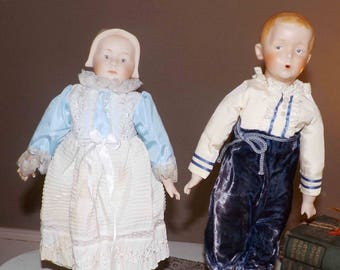 Vintage (1984) Porcelain bisque handmade, jointed doll. Boy or girl in period   Amish dress on stands for display. Signed.