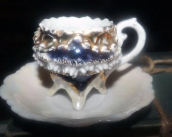 Early mid-century (attributed 1940s) German barbotine four-footed demitasse cup and saucer. Lusterware cobalt details. Flawed (see below).