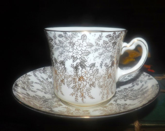 Early mid-century Vanderwood hand-painted gold floral chintz cup and saucer set made in England. Gold florals on pink.