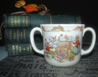 Vintage (1984) Royal Doulton Bunnykins double-handled child's loving cup | mug. Bunnies on the player piano and skipping rope.