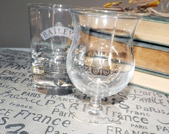 Pair of vintage Baileys Irish Cream glasses small snifter w/gold logo and tulip-shaped whisky glass with etched white logo and banner.
