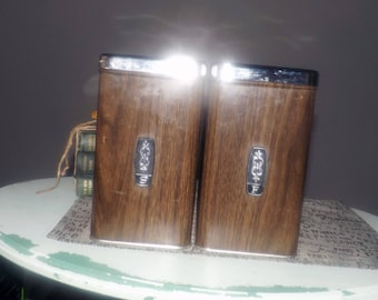 Pair of vintage (1970s) EKCO brown faux woodgrain finish canisters: one sugar, one flour.  Chrome lids, black pull tops.  Made in Canada.