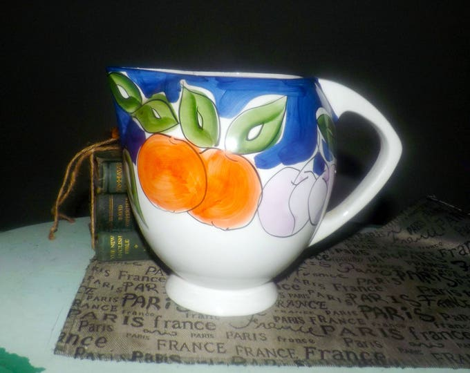 Vintage (1980s) Tabletops Unlimited Tutti Frutti pattern large, 64-ounce pitcher.  Hand-painted, stylized fruits, blue border.