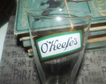 Vintage (1970s) O'Keefes Ale etched-glass pilsner beer half-pint or sampler glass. Old green and gold O'Keefe's logo.