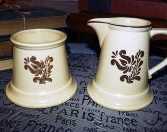 Vintage (1976) Pfaltzgraff Village stoneware creamer or open sugar bowl.  Brown American Folk Art on a tan ground.  Made in USA.