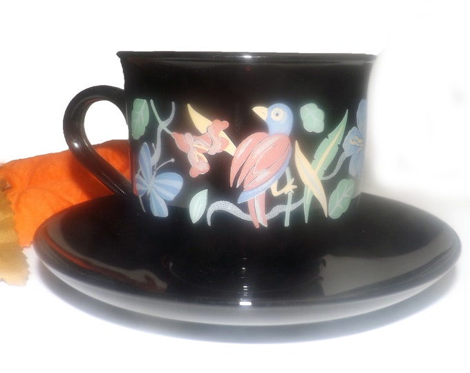 Vintage (1970s) Arcoroc cup and saucer set. Black glass with multicolor florals and birds. Made in France.