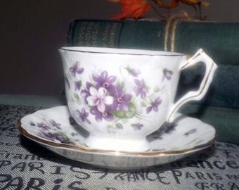 Vintage (1960s) Aynsley England Violette pattern tea set (footed cup with matching saucer). Violets, white ground, gold edge, accents.