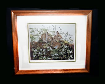 Vintage (1989) Joyce Bridgett framed matted numbered print of three bunnies in woodland. Print 1075 of 2950.