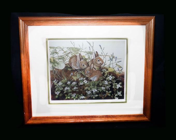 Vintage (1989) Joyce Bridgett framed matted numbered print of three bunnies in woodland. Print 1075 of 2950.