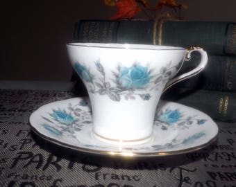 Early mid-century (1952) Aynsley tea set (flat corset-shaped cup with saucer). Blue roses, gray leaves, scalloped gold edge, accents