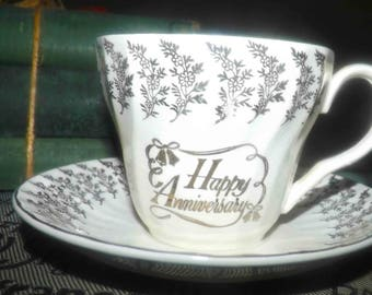 Vintage (1960s) H. Aynsley & Co. Happy Anniversary tea set (flat cup with matching saucer). Golden flowers, wedding bells, swirled body.