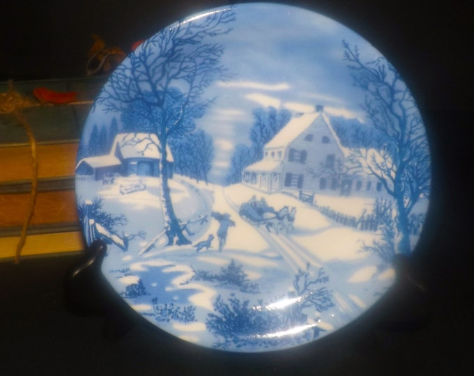 Vintage blue-and-white Currier & Ives Christmas salad or side plate. Horse sleigh, boy, dog winter landscape imagery.