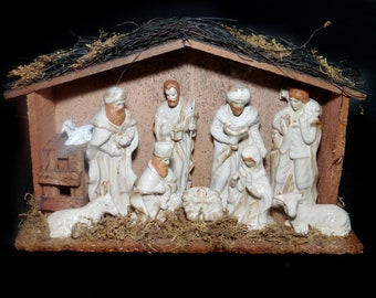 Vintage (1980s) Nativity Set. Ten porcelain figures in wooden shed with thatched roof. Figures are fixed in place. EBCI Imports.