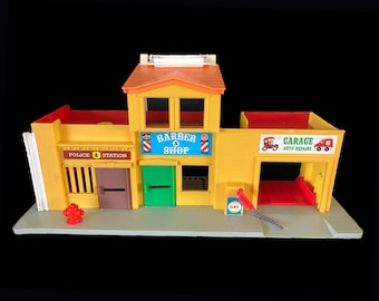 Vintage (1973) Fisher Price No. 6 Garage, Barber Shop, Police Station play set with convenient carry handle.