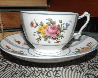Antique (early 1900s) Crown Staffordshire hand-painted tea set (footed cup with saucer). Multicolor florals, blue bands, enamel rim.