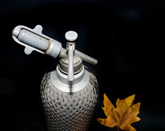 Mid-century Sparklets heavy-glass, wire-mesh covered Seltzer bottle made in Czechoslovakia.  Aluminum-zinc alloy head