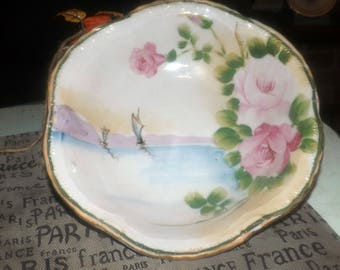 Antique (pre 1910) hand-painted Nippon bowl with a water | shore scene featuring sailboats, large bursts of pink roses. Gold edge.