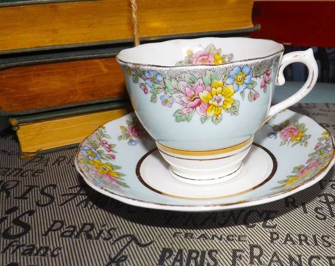 Mid-century (1950s) Colclough tea set (cup with matching saucer). Broad bands of baby blue, multicolor florals, gold edge and accents.