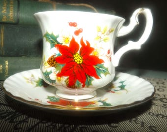Vintage (1976) Royal Albert Poinsettia Christmas tea set (footed cup with saucer). Red, white poinsettias, pine cones, gold edge.