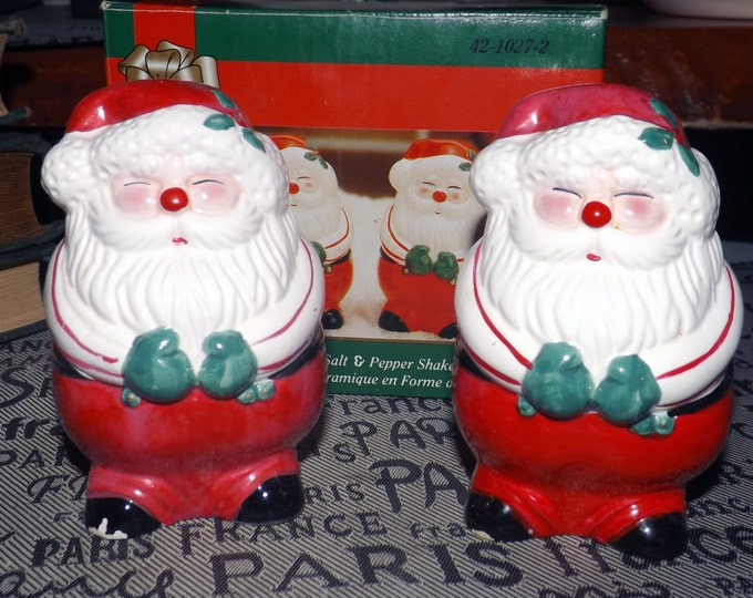 Vintage (1970s) Santa Claus salt and pepper shakers. Santa in green mitts and suspenders, red pants & toque with holly. Hand painted. Japan