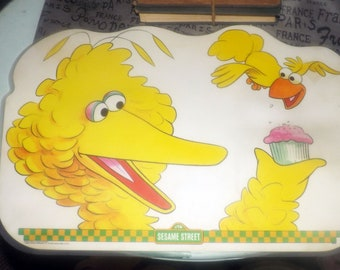 Vintage (1982) Sesame Street Big Bird child | baby | toddler plastic placemat. Big Bird with cupcake on front, games and puzzles to reverse.