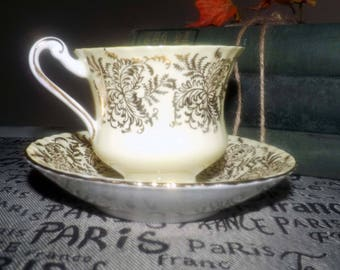 Vintage (1960s) Paragon | Royal Paragon A3068 tea set (footed cup with saucer).  Yellow verge, gold filigree, center florals, gold edge.
