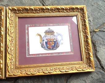 Pair of vintage (1980s) heavy gilt-framed and matted prints of a fancy Imari teapot and tea cup.  Signed V. Morland.