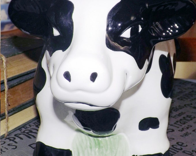 Vintage (1992) Boston Warehouse figural cookie jar in the shape of a smiling, black-and-white spotted cow.