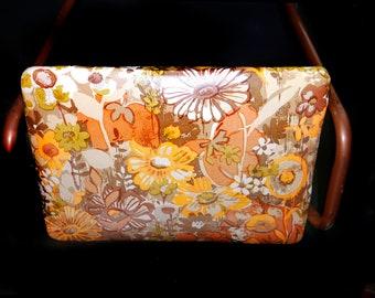 Retro vintage (1970s) flower power vanity bench. Metal frame with vinyl seat in orange, brown, green and yellow.