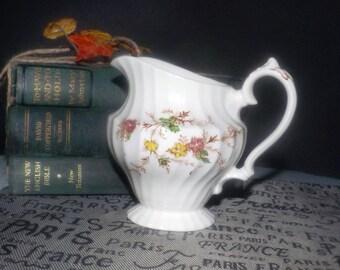 Mid-century (1950s) Myott Heritage M411PU pattern creamer | milk jug. Swirled body shape, multicolor red and yellow florals.