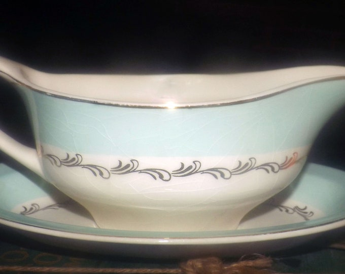 Mid-century Johnson Brothers JB917 hand-decorated gravy boat with oval under-plate. Aqua band, gold scrolls and edge.