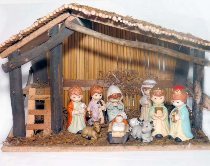 Vintage twelve-piece Nativity Set | creche scene. Eleven porcelain bisque figures and handmade shed with thatched roof.