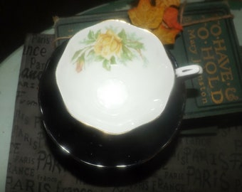 Early mid-century Royal Albert black tea set (footed cup with matching saucer) made in England. Yellow roses, greenery, gold edge.