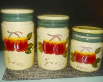 Set of 3 vintage (1980s) Casa Elite canisters. Hand-painted with red apples and the wording Pommes Apples. Vacuum-sealed lids.