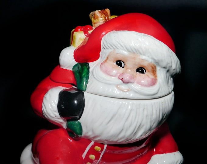Vintage ceramic Frosty Santa Claus Christmas cookie jar.  Santa going down the chimney with sack of presents.
