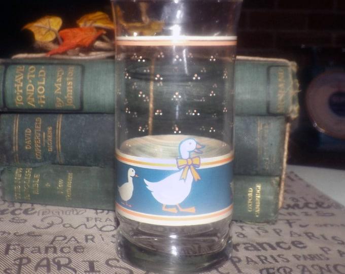 Vintage (1980s) tumbler   water glass. White goose, blue band, yellow ribbon, peach band, raindrops.