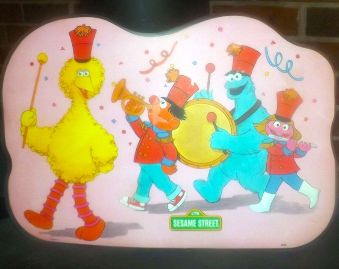 Vintage (1982) Sesame Street child | baby | toddler plastic placemat. Big Bird, Elmo, Ernie join in the parade. games, puzzles reverse.