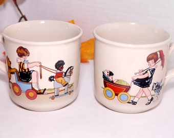 Pair of vintage (1980s) Die Spiegelburg children's handled mugs. Walking the Baby, Rocking Horse. Made in Germany.