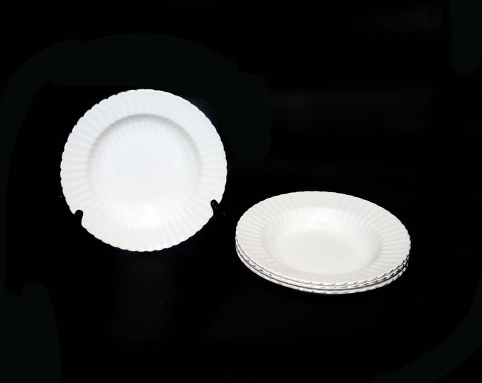 Set of four mid-century Paragon 497 rimmed soup bowls made in England. All white with a fluted rim and platinum edge.