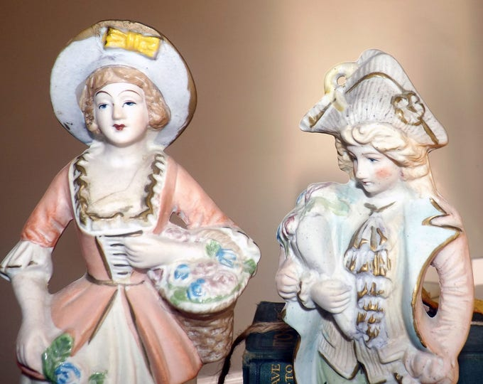 Pair of early mid-century porcelain bisque figures. Man and woman in period dress. Made in Occupied Japan.