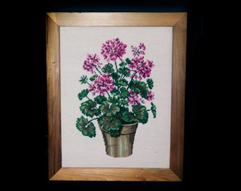 Vintage (attributed 1960s) framed needlepoint art on burlap. Pink geraniums in pot. Solid wood frame.