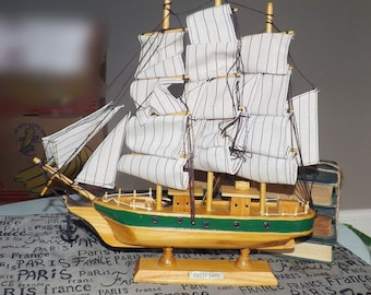 Vintage (1960s | 1970s) wooden model of the Cutty Sark sailing ship. Brass name plate, fabric sails, anchor, wooden base.