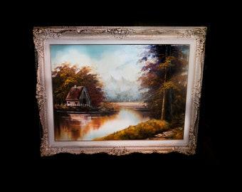 Mid century original oil on canvas signed Lamont. Elaborate carved gilt wood frame. Forest, river, cabin landscape.