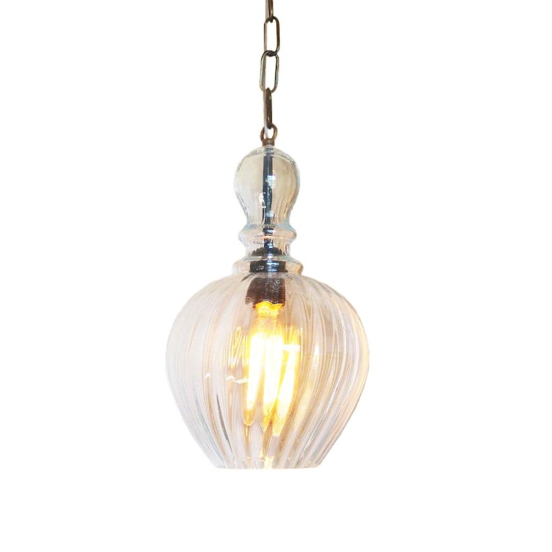 Pendant glass lighting fixture hanging on a brass chain  Pawn shape blown  glass shade, hanging on a brass chain, from a ceiling canopy